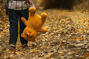Autism reversed - photo of child carrying teddy upside down
